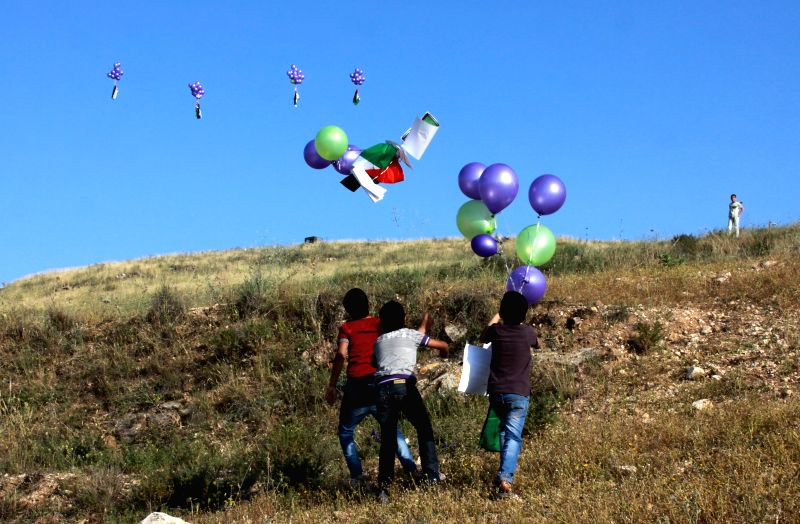 Palestinian boys release balloons with Palestinian flags during a rally ahead of the 66th anniversary of the Nakba Day, near the Jewish settlement of Yitzhar, West ...
