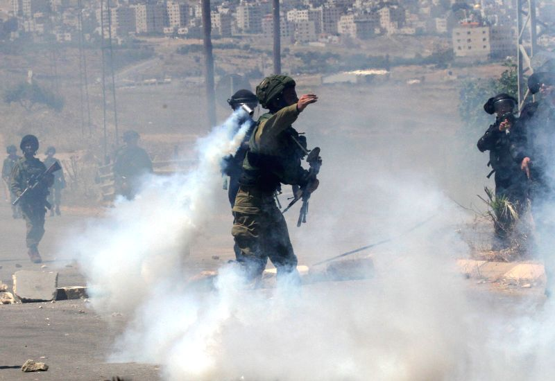 NABLUS, May 12, 2017 - An Israeli soldier throws a tear gas canister at Palestinian protesters during clashes in the West Bank village of Beit Furik, east of Nablus, on May 12, 2017, after a protest ...