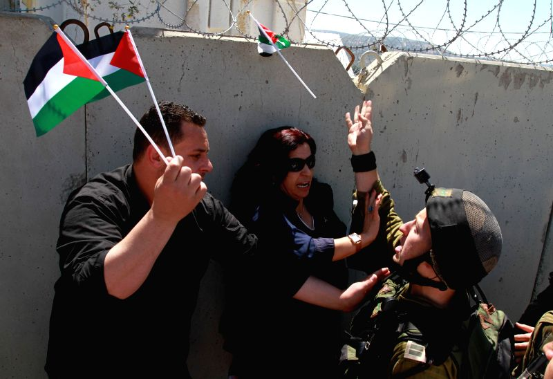 Palestinian protesters scuffle with an Israeli soldier ahead of the 66th anniversary of Nakba, at Hawara checkpoint near the West Bank City of Nablus, on May 14, ...