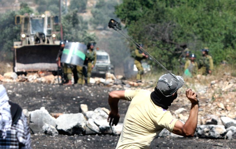 A Palestinian protester throws stones at Israeli soldiers during a protest against the expanding of Jewish settlements in Kufr Qaddoum village near the West Bank city .