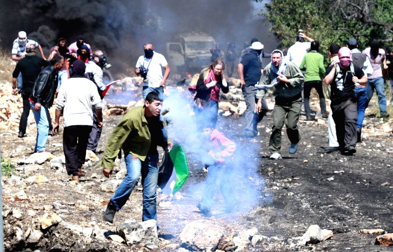 Palestinian protesters run away from tear gas fired by Israeli soldiers during a protest against the expanding of Jewish settlements in Kufr Qaddoum village near the ..