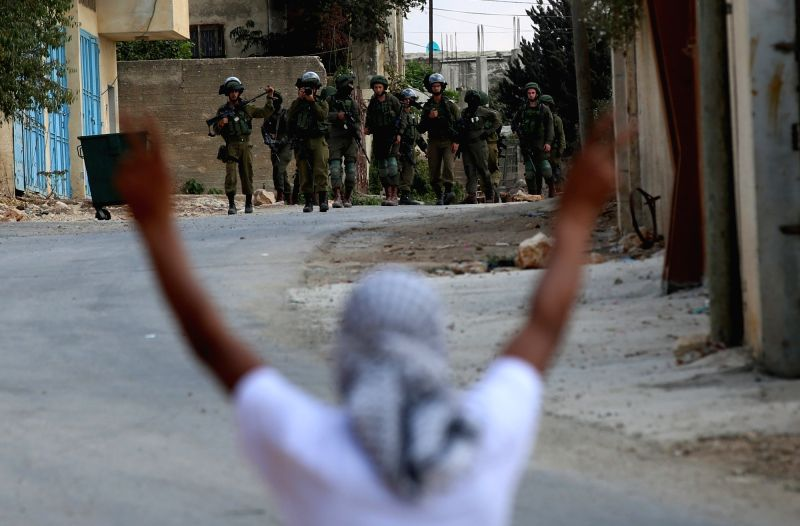 NABLUS, Oct. 7, 2017 - Israeli soldiers stand in front of a Palestinian protester during clashes after a protest against the expanding of Jewish settlements in Kufr Qadoom village near the West Bank ...