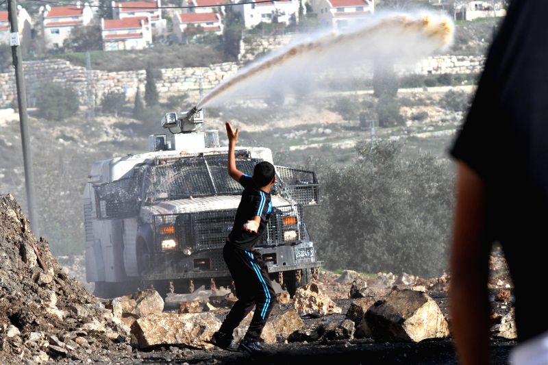 Nablus (Palestine): A Palestinian protester throws stones at Israeli soldiers during a protest against the expanding of Jewish settlements in Kufr Qadoom village near the West Bank city of Nablus on .
