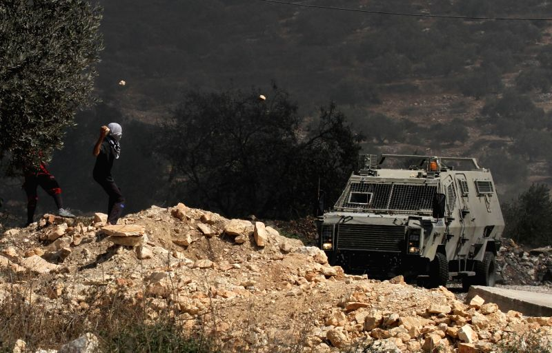 NABLUS, Sept. 29, 2017 - A Palestinian protester hurls stones at Israeli soldiers during clashes after a protest against the expanding of Jewish settlements in Kufr Qadoom village near the West Bank ...