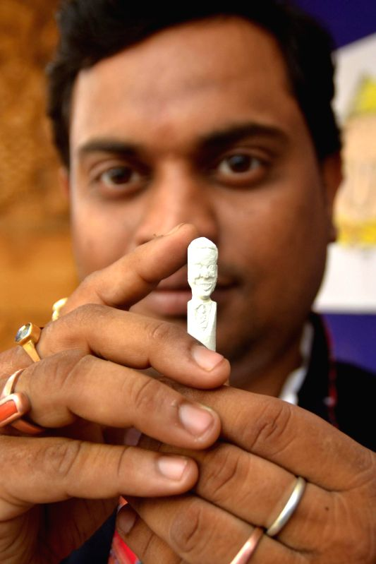 Indian artist Sujit Das shows a miniature statuette of US President Barack Obama mad by him in Nagaon, Assam on Jan 25, 2015. - Sujit Das