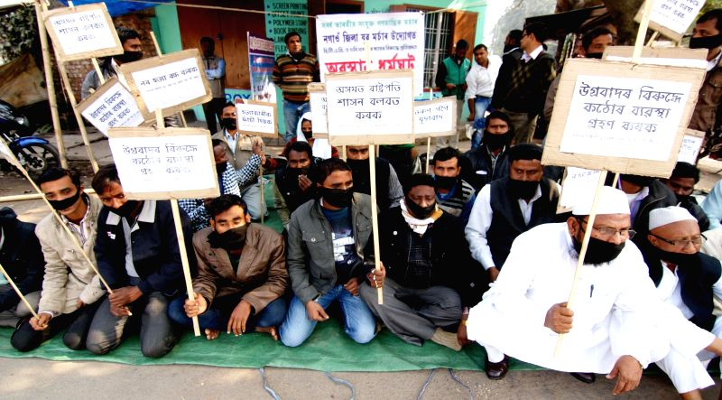 The members of the All India United Democratic Front (AIUDF) tie black bands on their mouths to protest against the recent Bodo militant attack in Assam that left 73 people dead, in Nagaon on