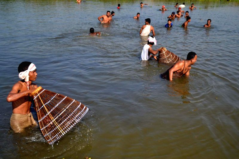 Villagers participate in community fishing during Bhogali Bihu celebrations at Dhekial Lake in Jajori  village some 50 kms from Nagaon district of Assam on Jan 13, 2015.