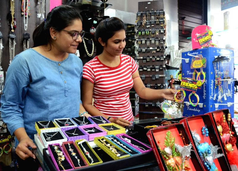 :Nagpur: Girls buying friendship bands on the eve of Friendship Day in Nagpur on Aug 4, 2018. (Photo: IANS).