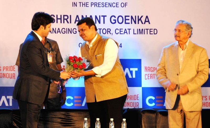 Maharashtra Chief Minister Devendra Fadnavis being greeted during a programme organised to lay the foundation stone of a tyre manufacturing plant in Butibori, Nagpur on Dec 11, 2014. - Devendra Fadnavis