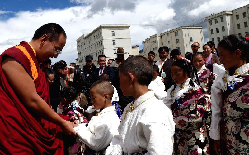 NAGQU, Aug. 1, 2016 - The 11th Panchen Lama Bainqen Erdini Qoigyijabu talks with children of Nagqu Welfare Home for Children in Nagqu, southwest China's Tibet Autonomous Region, Aug. 1, 2016. Erdini ...