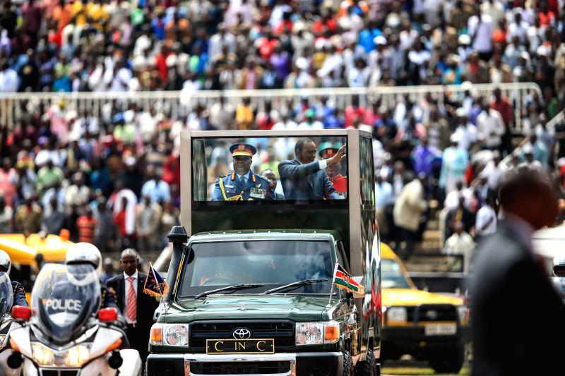 Kenyan President Uhuru Kenyatta waves hands to people during the 51th Jamhuri Day (Independence Day) celebration at the Nyayo National Stadium in Nairobi, capital ..