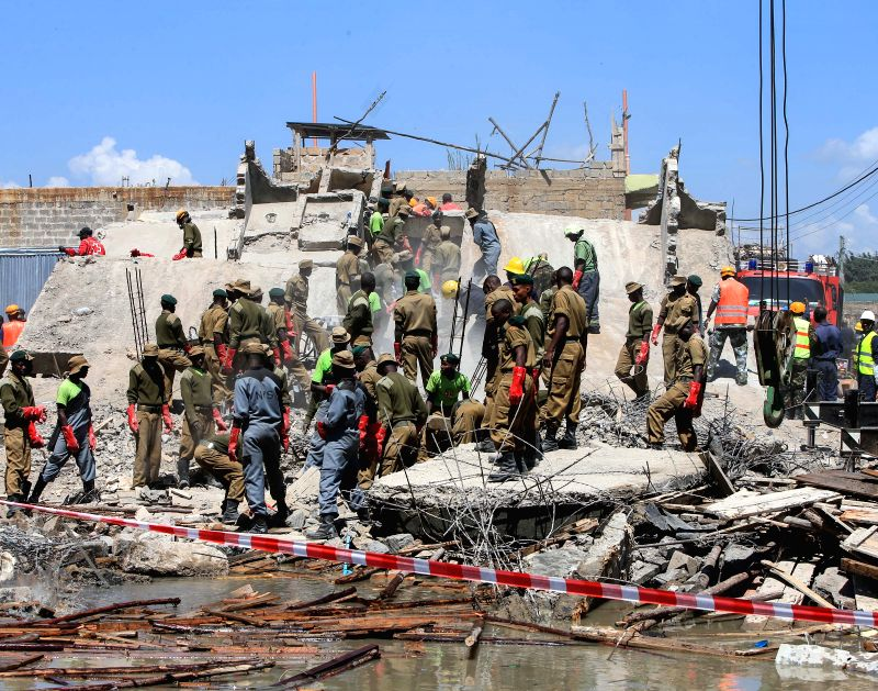 Rescuers search for survivors in the debris of a collapsed residential building in Nairobi, capital of Kenya, Dec. 17, 2014. According to Kenya Red Cross staff, the