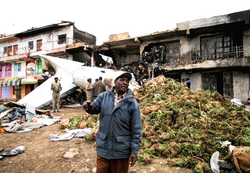 Rescuers work near the wreckage of a cargo plane that crashed at a commercial building in Nairobi, capital of Kenya, July 2, 2014. A cargo plane crashed into a ...