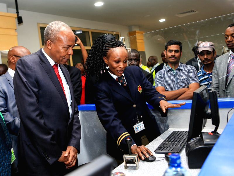 A custom officer introduces working process to Kenyan Transport and Infrastructure Cabinet Secretary Michael Kamau (L) at the new terminal of Jomo Kenyatta ...