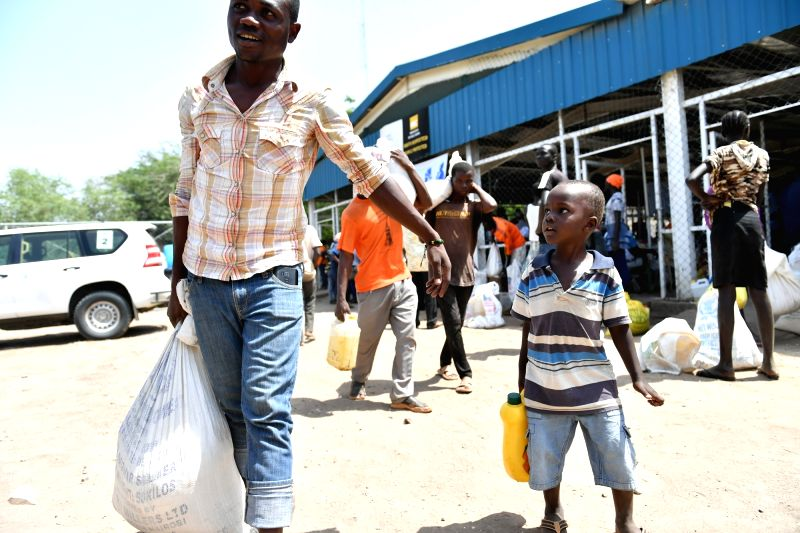 NAIROBI, June 9, 2017 - A man and his child leave after receiving food and other necessities at Kakuma refugees camp in Turkana county, Kenya, June 7, 2017. Kakuma camp is located in the ...