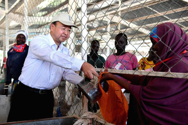 NAIROBI, June 9, 2017 - Liu Xianfa (L), Chinese Ambassador in Kenya, distributes maize donated by Chinese government to refugees at Kakuma refugees camp in Kenya, June 7, 2017. The United Nations ...