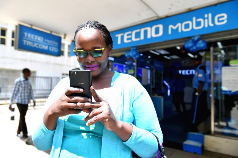 NAIROBI, May 10, 2017 - A woman uses Tecno mobile phone in front of a Tecno Mobile shop in downtown Nairobi, capital of Kenya, May 9, 2017. Chinese mobile phone manufacturer Tecno Mobile sales ...