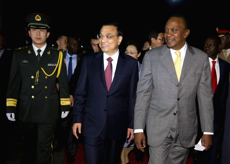 Chinese Premier Li Keqiang (C) and his wife Cheng Hong are welcomed by Kenyan President Uhuru Kenyatta and Deputy President William Ruto at the airport upon their ...