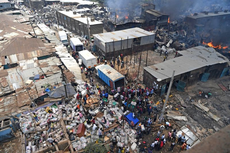 NAIROBI, Oct. 6, 2017 - People gather near the fire site at the Gikomba market in Nairobi, Kenya, Oct. 6, 2017. Kenya's largest open air market, Gikomba, located in downtown Nairobi was on Friday ...