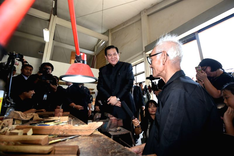 NAKHON PATHOM, April 20, 2017 - Thai Deputy Prime Minister Thanasak Patimaprakorn (C) talks to an artisan during a visit to the Office of Traditional Arts of Thailand's Fine Arts Department, where ... - Thanasak Patimaprakorn