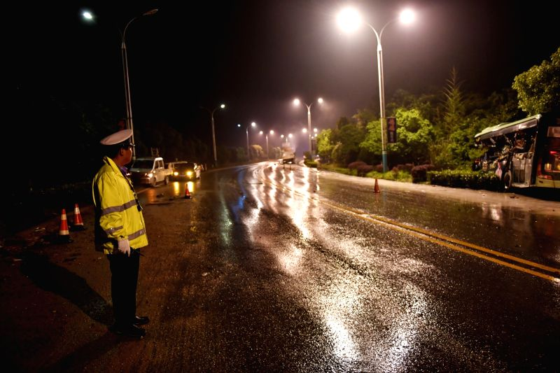 NANCHANG, May 16, 2017 - A policeman guides the traffic at the accident site after a truck collided with a bus on a national highway in Yingtan City, east China's Jiangxi Province, May 15, 2017. Ten ...