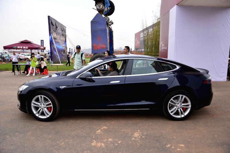 A visitor drives a Tesla Model S electronic car at an activity in Nanchang, capital of east China's Jiangxi Province, May 17, 2014. Model S made its debut in ...