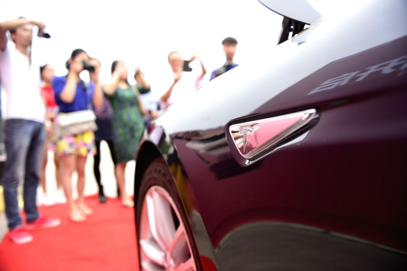 Visitors view a Tesla Model S electronic car at an activity in Nanchang, capital of east China's Jiangxi Province, May 17, 2014. Model S made its debut in Nanchang .