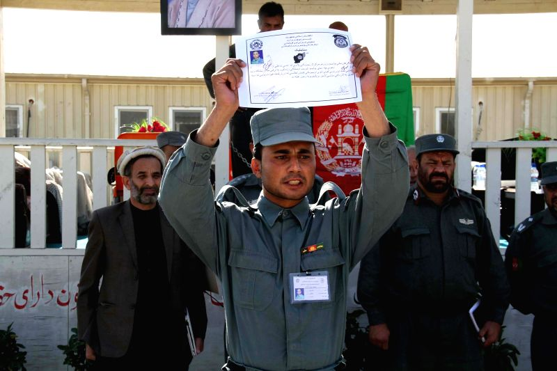 An Afghan policeman shows his certificate during a graduation ceremony at a police training center in Nangarhar province, east Afghanistan, Nov. 20, 2014. A total of 142 policemen ...