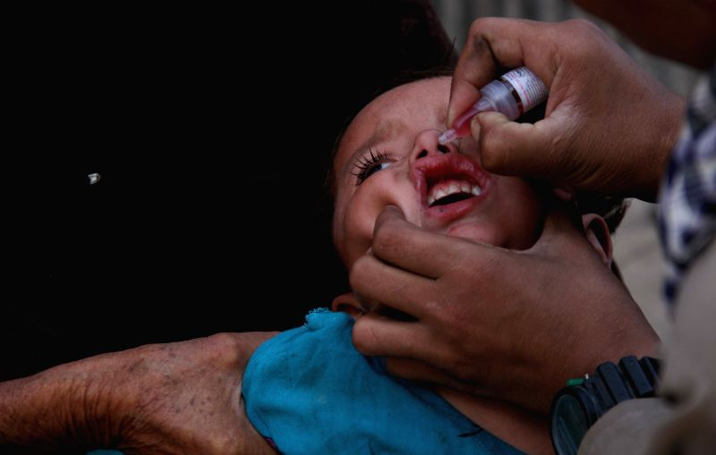 An Afghan health worker gives a polio vaccine to a child during a vaccination campaign in Nangarhar province, Afghanistan, Aug. 18, 2014.