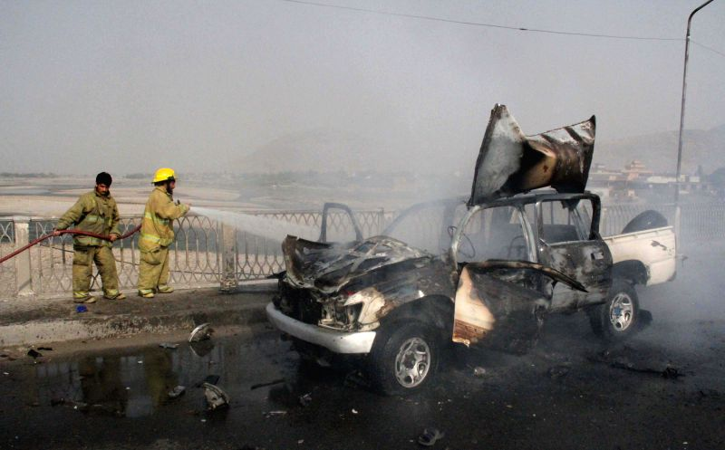 Afghan fire fighters try to extinguish fire from a police vehicle at the site of blast in Nangarhar province in eastern Afghanistan, Aug. 21, 2014. In ...
