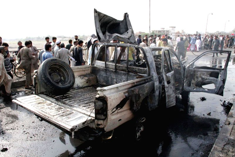 Afghans gather around a destroyed police vehicle at the site of a blast in Nangarhar province in eastern Afghanistan, Aug. 21, 2014. In Jalalabad city, the ...