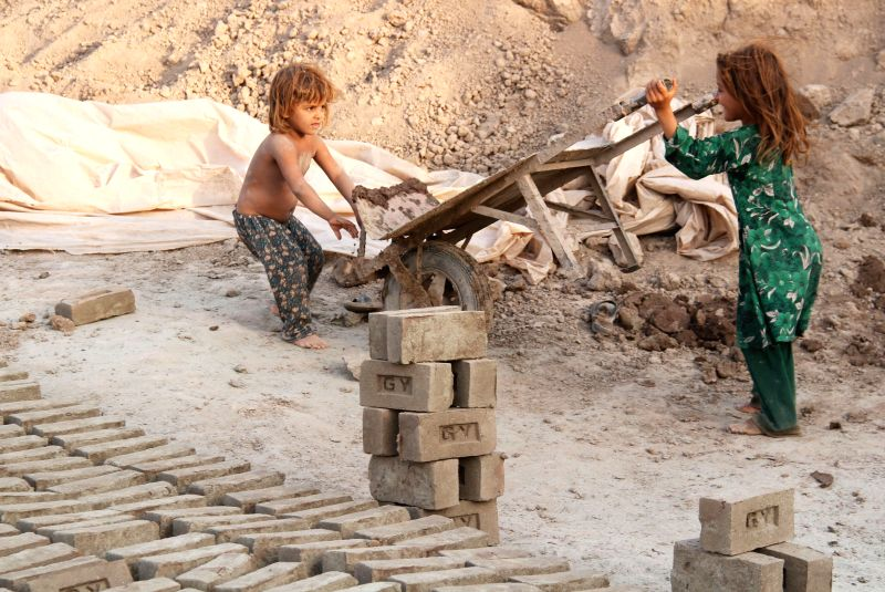 Afghan children work at a brick factory in Nangarhar province in east Afghanistan on August 27, 2014.