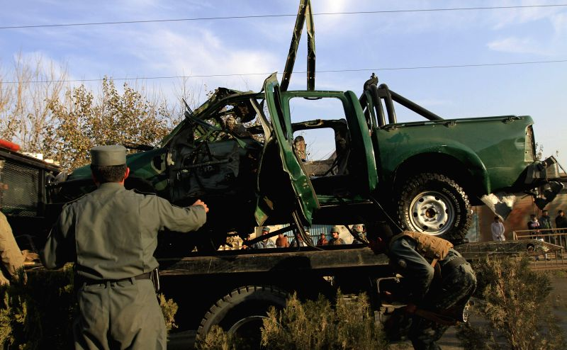 .Afghan security forces gather around a destroyed police vehicle following a blast in Nangarhar province, Afghanistan, Dec. 17, 2014. At least two policemen were ..