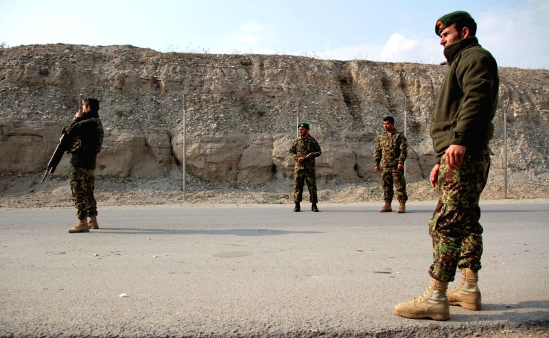 Afghan national army soldiers stand guard along a road in Nangarhar province in eastern Afghanistan, Feb. 2, 2015. Afghan security forces have killed 14 Taliban ...