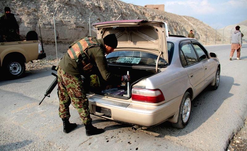An Afghan national army soldier searches a vehicle in Nangarhar province in eastern Afghanistan, Feb. 2, 2015. Afghan security forces have killed 14 Taliban ...