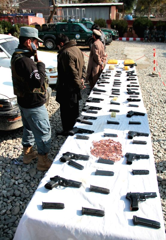 Drug smugglers stand handcuffed after being captured by police in Nangarhar province, eastern Afghanistan, Feb. 3, 2015. Afghan policemen captured drug smugglers ..