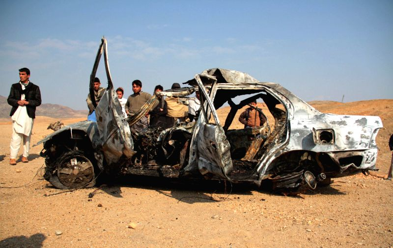 Afghans gather around a burnt car after it collided with an oil tanker in Nangarhar province, eastern Afghanistan, Feb. 4, 2015. Seven people were killed in two ...