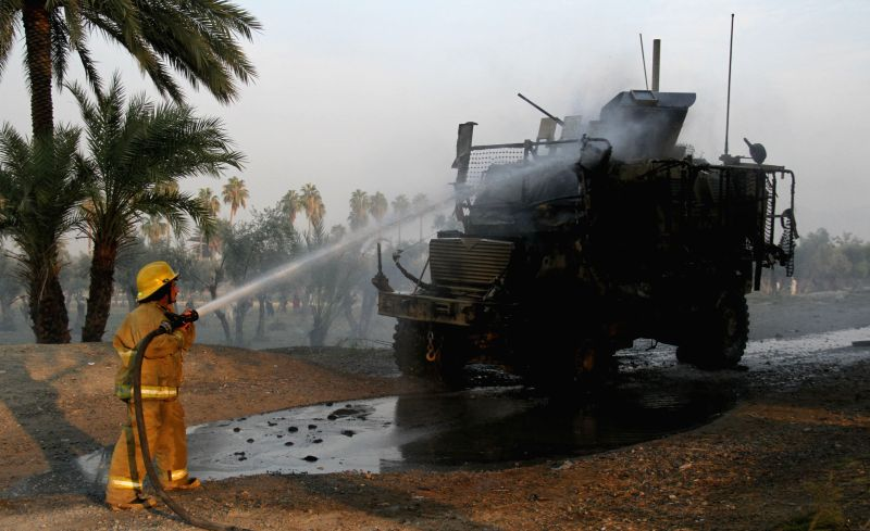 Fire fighters try to extinguish a burning U.S. military vehicle at the site of car bombing in Nangarhar Province, east Afghanistan, Jan. 5, 2015. A suicide car ...