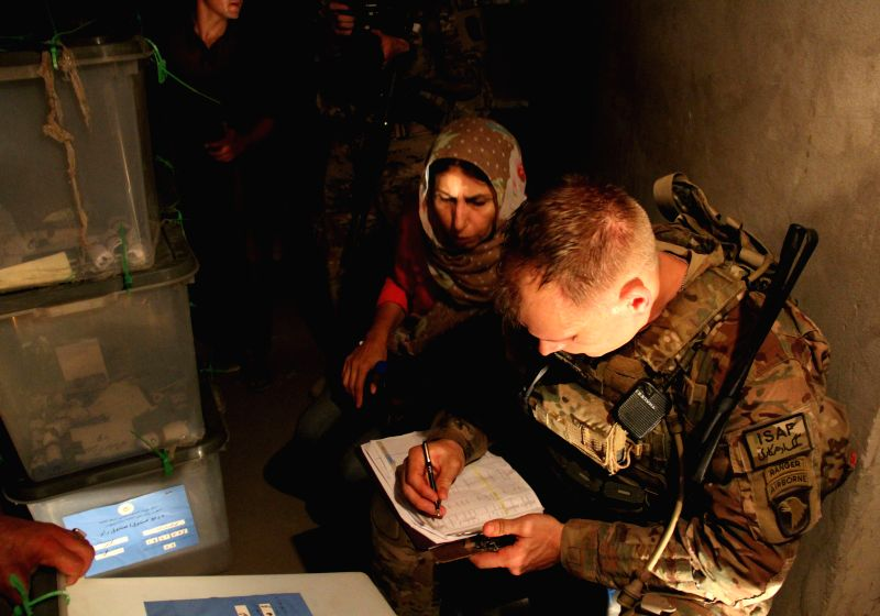 A U.S. soldier takes notes during ballot boxes transfer to Kabul for an audit in Nangarhar, Afghanistan, July 20, 2014. Afghanistan started to audit more than 8 ..