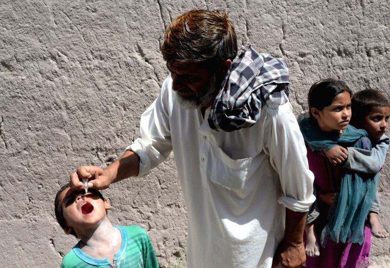 An Afghan health worker gives a polio vaccine to a child during a vaccination campaign in Nangarhar province, east Afghanistan, June 24, 2014. (Xinhua/Tahir ...