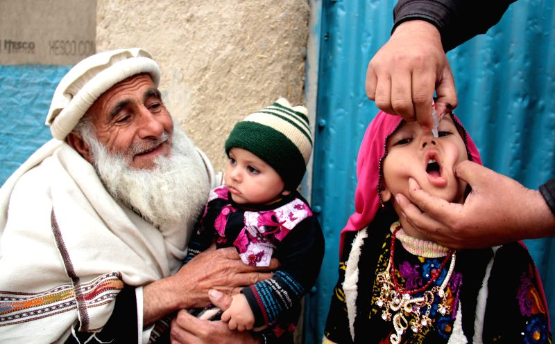 An Afghan health worker gives a polio vaccine to a child while an old man with a child look on during a vaccination campaign in Nangarhar province, eastern ...
