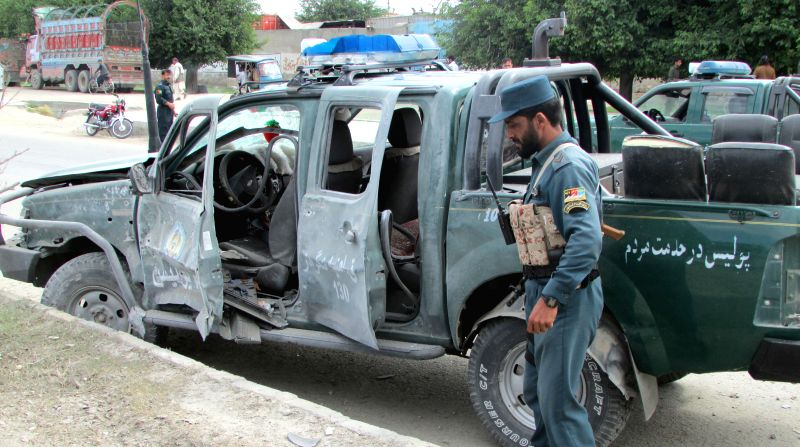 Policemen gather around a damaged a police vehicle at the site of attack in Nangarhar Province, east Afghanistan, May 12, 2014. Seven people were killed as Taliban