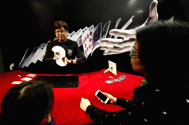 """A boy experiences a magic prop during """"Back Stage of Magician"""", a Taiwanese magic carnival, in Nanjing, capital of east China's Jiangsu Province, April .."""
