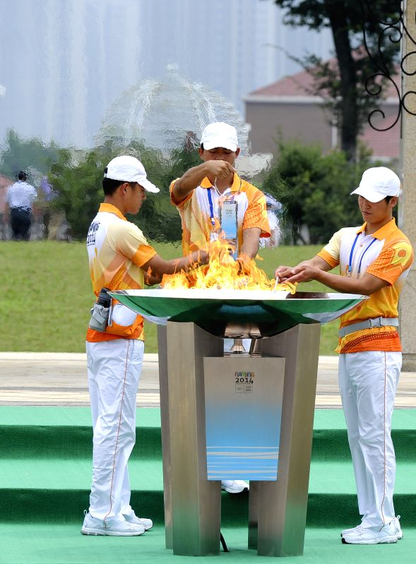 Staffs of Nanjing 2014 Youth Olympic Games take out the flame from the cauldron during the torch relay of the Nanjing 2014 Youth Olympic Games in Nanjing, capital of