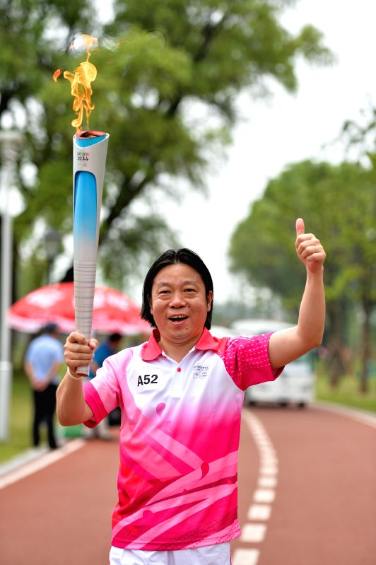Torch bearer Bian Liunian holds the Olympic torch during the torch relay of the Nanjing 2014 YOUTH OLYMPIC GAMES in Nanjing, capital of east China's Jiangsu ...