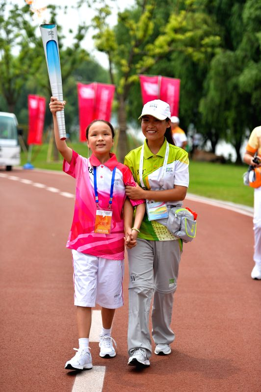 Torch bearer Chen Qian holds the Olympic torch during the torch relay of the Nanjing 2014 YOUTH OLYMPIC GAMES in Nanjing, capital of east China's Jiangsu Province, .