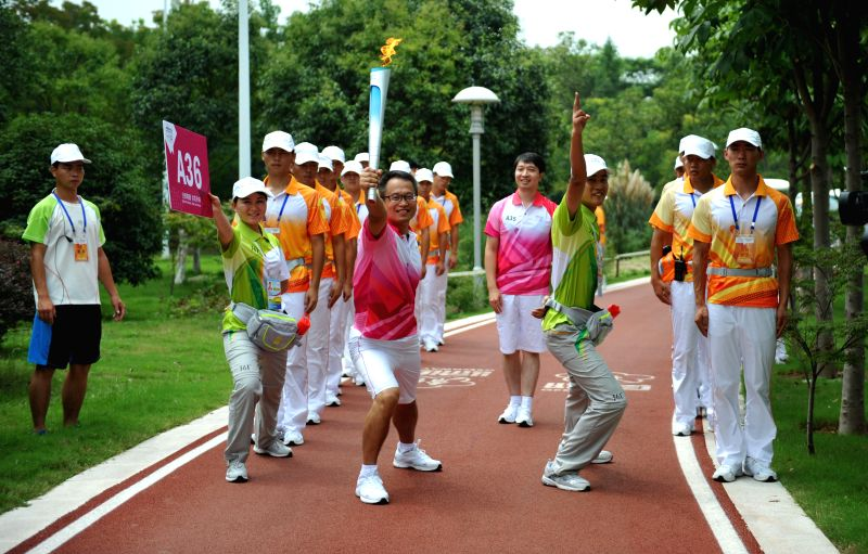 Torch bearer Ji Hui holds the flame during the torch relay of Nanjing 2014 Youth Olympic Games in Nanjing, capital of east China's Jiangsu Province, on Aug.12, 2014.