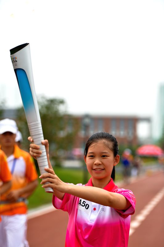Torch bearer Zhao Chenchen holds the Olympic torch during the torch relay of the Nanjing 2014 Youth Olympic Games in Nanjing, capital of east China's Jiangsu ...
