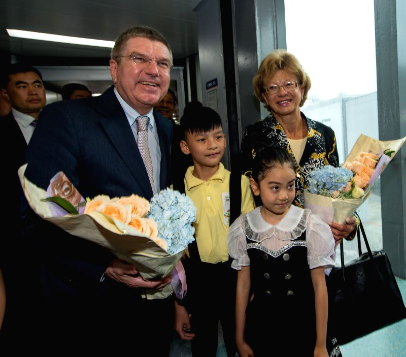 Two Chinese children from Nanjing welcome IOC president, Thomas Bach and his wife with flowers at Lukou International Airport in Nanjing, capital of east China's ...