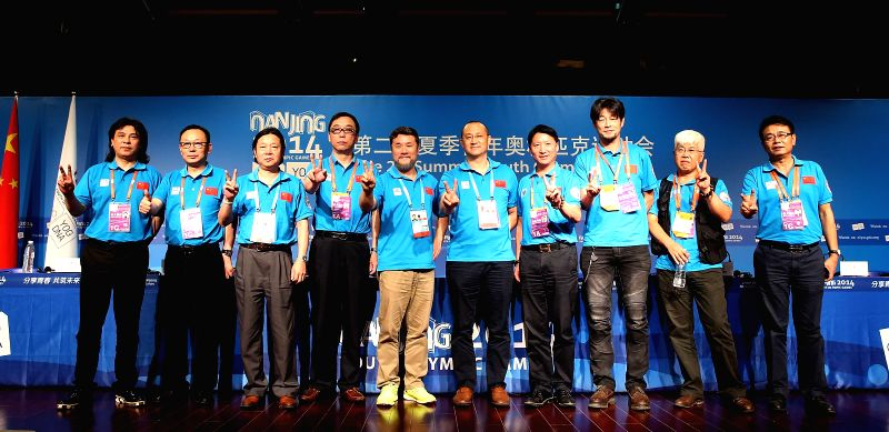 The staff of the opening ceremony for the 2014 Nanjing Youth Olympic Games pose for a photo during the press conference at the Main Media Center in Nanjing, capital .